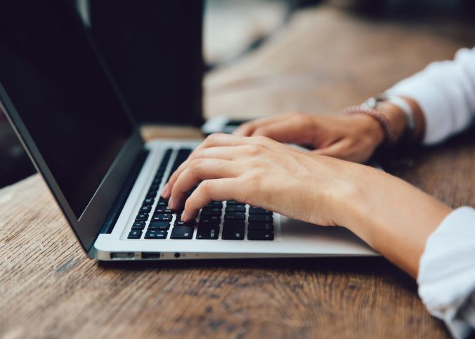 Mãos femininas digitando em um teclado de notebook. | O que é e por que criar um site? - Superbiz